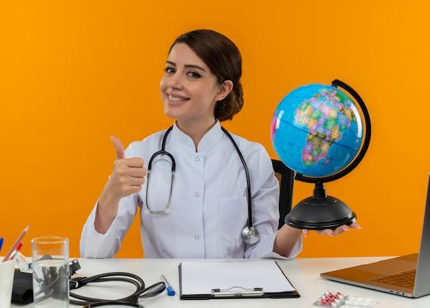 Улыбающаяся молодая женщина-врач в медицинском халате со стетоскопом, сидя за столом, работает на компьютере с медицинскими инструментами, держа глобус ее большим пальцем на изолированном желтом фоне