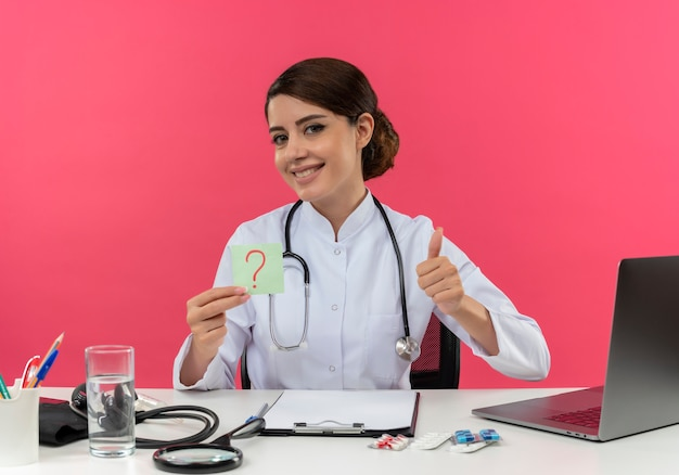 Улыбающаяся молодая женщина-врач в медицинском халате со стетоскопом, сидя за столом, работает на компьютере с медицинскими инструментами, держа вопросительный лист, отметив ее большой палец вверх на розовой стене