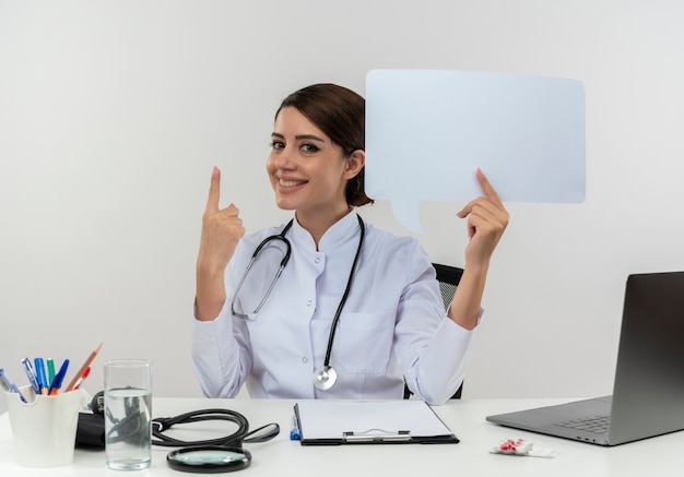 Smiling young female doctor wearing medical robe with stethoscope sitting at desk work on computer with medical tools holding chat bubble poiunts to up with copy space
