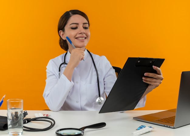 Smiling young female doctor wearing medical robe with stethoscope sitting at desk work on computer with medical tools holding and looking at clipboard and putting pen on cheek on yellow wall