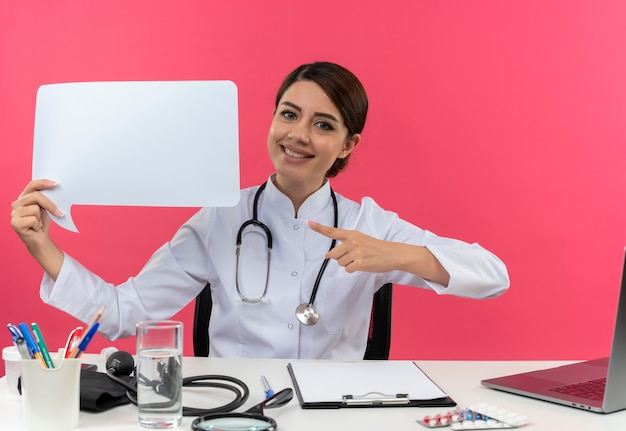 Smiling young female doctor wearing medical robe with stethoscope sitting at desk work on computer with medical tools holding and points to blank chat bubble on pink wall