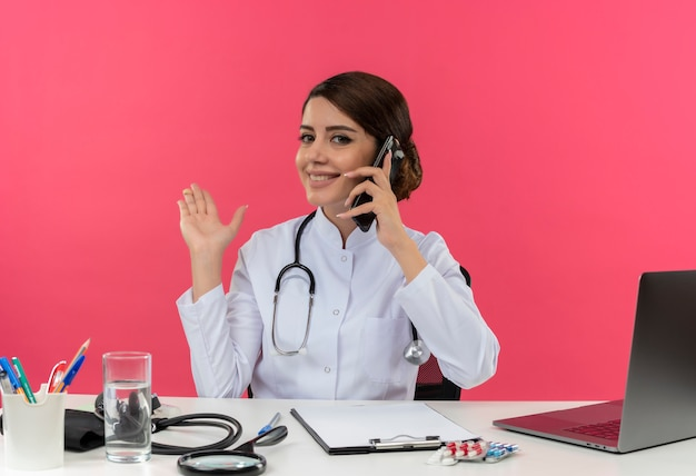 Smiling young female doctor wearing medical robe with stethoscope sitting at desk work on computer with medical tools speaks on phone and points with hand to side on pink wall