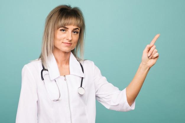 Улыбающаяся молодая женщина-врач со стетоскопом указывает пальцами на синее пространство