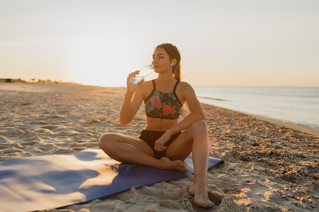 Smiling young female drinking fresh water and listening music in headphones after training. young athletic woman exercising near the sea . summer sunset.