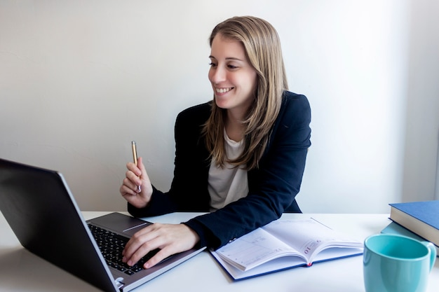 Smiling young female entrepreneur sitting at home working with her laptop