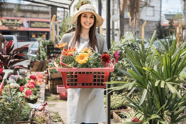 Smiling young female gardener holding colorful flowers in container