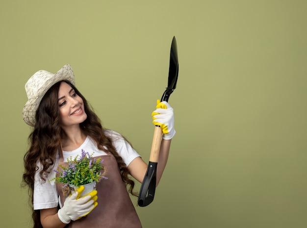 園芸帽子と手袋を身に着けている制服を着た若い女性の庭師の笑顔は植木鉢を保持し、オリーブグリーンの壁に分離されたスペードを見ます