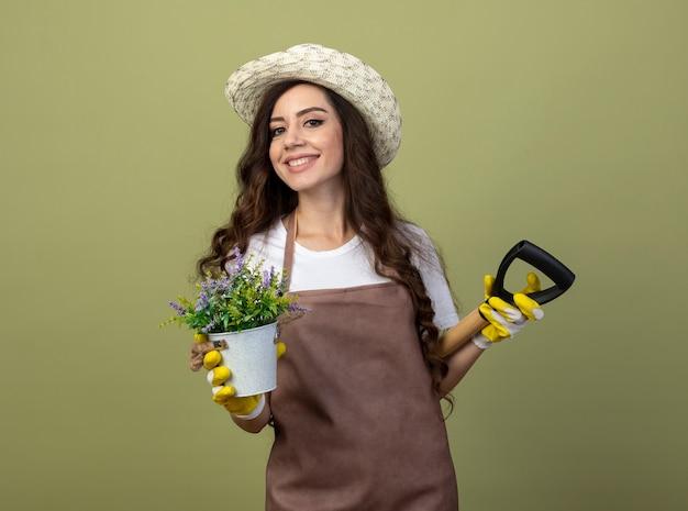 園芸帽子と手袋を身に着けている制服を着た若い女性の庭師の笑顔は、オリーブグリーンの壁に隔離された背中の後ろに植木鉢とスペードを保持します
