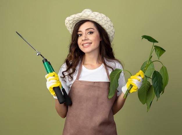 Улыбающаяся молодая женщина-садовник в униформе в садовой шляпе и перчатках держит ножницы для растений и садов, изолированные на оливково-зеленой стене с копией пространства