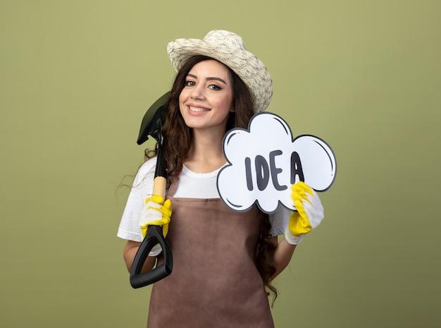 園芸帽子と手袋を身に着けている制服を着た若い女性の庭師の笑顔は、オリーブグリーンの壁に分離されたスペードとアイデアバブルを保持