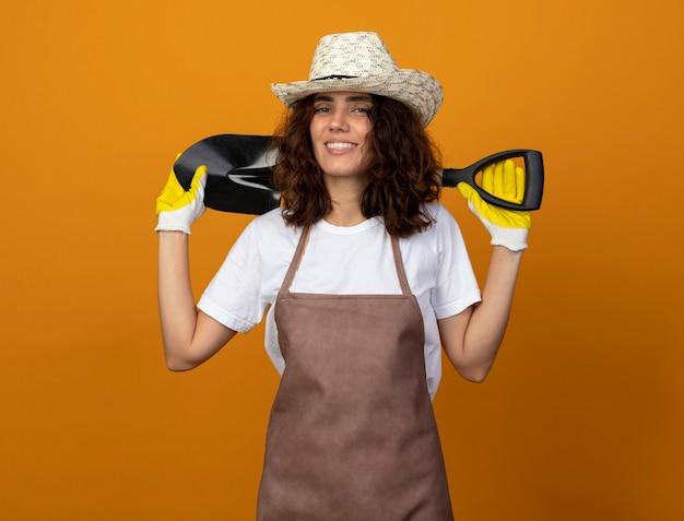 首の後ろにスペードを置くガーデニング帽子と手袋を身に着けている制服を着た若い女性の庭師の笑顔