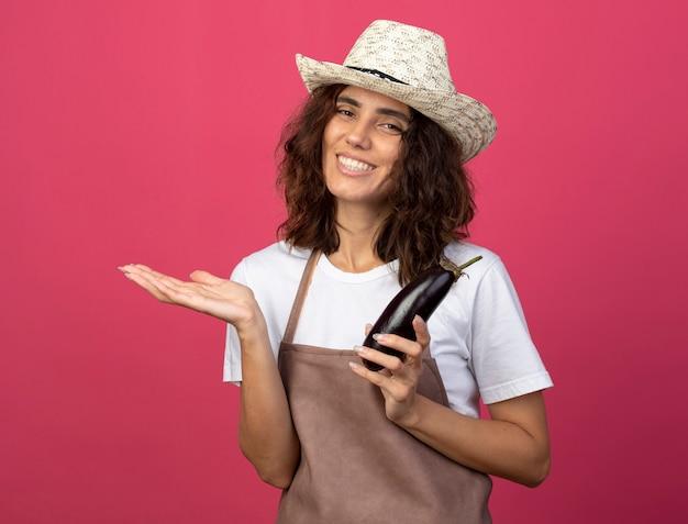 Улыбающаяся молодая женщина-садовник в униформе в садовой шляпе держит баклажан за руку