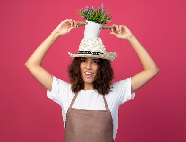 頭の上の植木鉢に花を保持しているガーデニング帽子を身に着けている制服を着た若い女性の庭師の笑顔