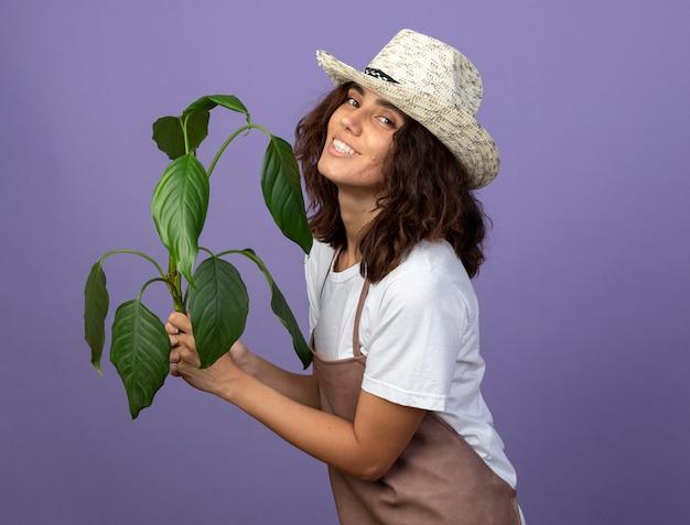 植物を保持している園芸帽子を身に着けている制服を着た若い女性の庭師の笑顔
