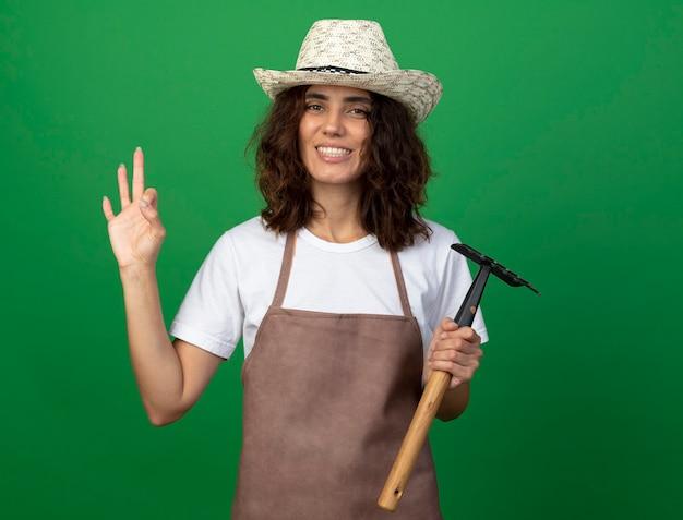 緑の壁に分離された大丈夫なジェスチャーを示す熊手を保持している園芸帽子を身に着けている制服を着た若い女性の庭師の笑顔