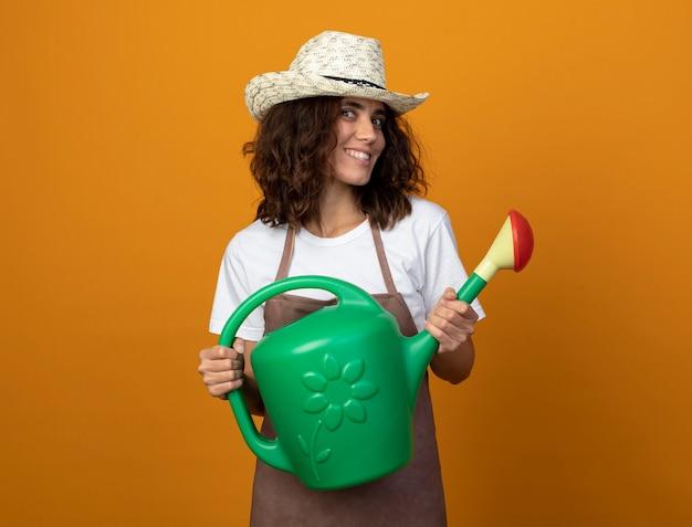 물을 수 들고 원예 모자를 쓰고 제복을 입은 젊은 여성 정원사 미소