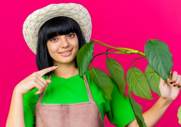 ガーデニング帽子をかぶって制服を着た若い女性の庭師の笑顔は、植物を保持し、ポイントします
