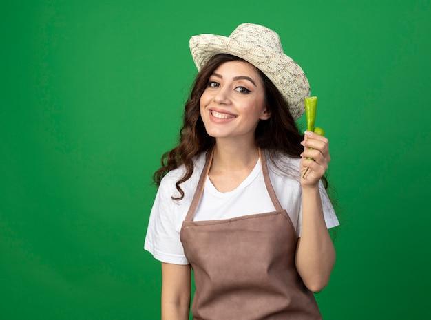 ガーデニング帽子をかぶって制服を着た若い女性の庭師の笑顔は、コピースペースで緑の壁に分離された壊れた唐辛子を保持