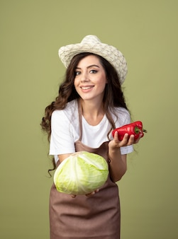 園芸帽子をかぶって制服を着た若い女性の庭師の笑顔は、オリーブグリーンの壁に分離されたキャベツと赤唐辛子を保持