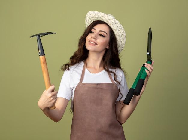 Улыбающаяся молодая женщина-садовник в униформе в садовой шляпе держит ножницы и смотрит на грабли, изолированные на оливково-зеленой стене