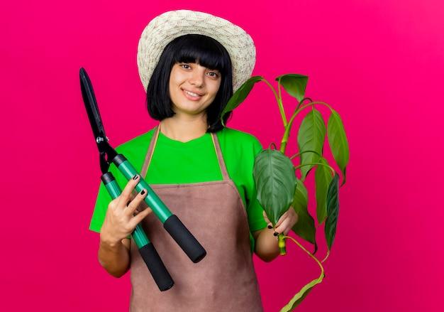 ガーデニング帽子をかぶって制服を着た若い女性の庭師の笑顔はクリッパーと植物を保持します