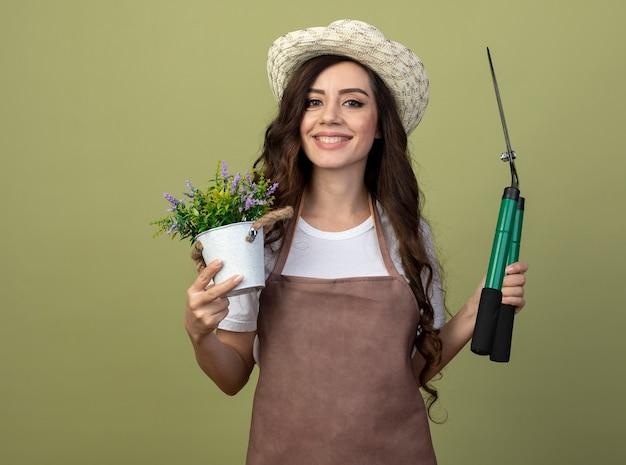 Улыбающаяся молодая женщина-садовник в униформе в садовой шляпе держит цветочный горшок и садовые ножницы, изолированные на оливково-зеленой стене с копией пространства