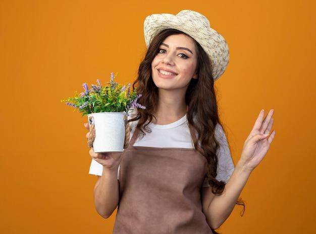 ガーデニング帽子をかぶった制服を着た若い女性の庭師の笑顔は、植木鉢を保持し、コピースペースでオレンジ色の壁に隔離された指で4つのジェスチャー