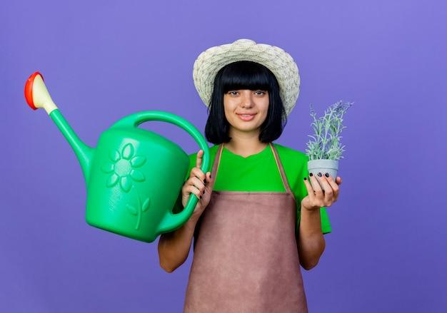 원예 모자를 쓰고 제복을 입은 젊은 여성 정원사는 화분을 보유하고 물을 수 있습니다.