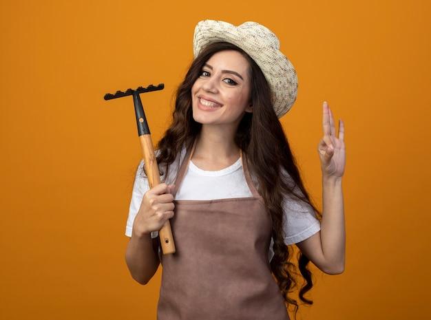 원예 모자를 쓰고 제복을 입은 젊은 여성 정원사 미소는 갈퀴를 보유하고 복사 공간이 오렌지 벽에 고립 된 확인 손 기호를 확인합니다.