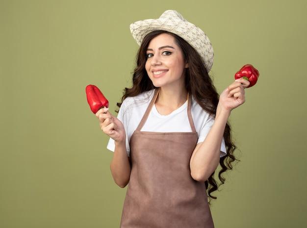 Улыбающаяся молодая женщина-садовник в униформе в садовой шляпе держит красный перец, изолированный на оливково-зеленой стене
