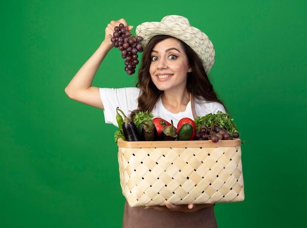 ガーデニング帽子を身に着けている制服を着た若い女性の庭師の笑顔は、緑の壁に隔離された野菜のバスケットとブドウを保持します