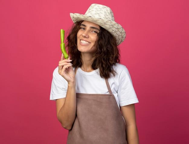 Sorridente giovane giardiniere femminile in uniforme che indossa il cappello da giardinaggio tenendo la rottura del pepe isolato sul colore rosa