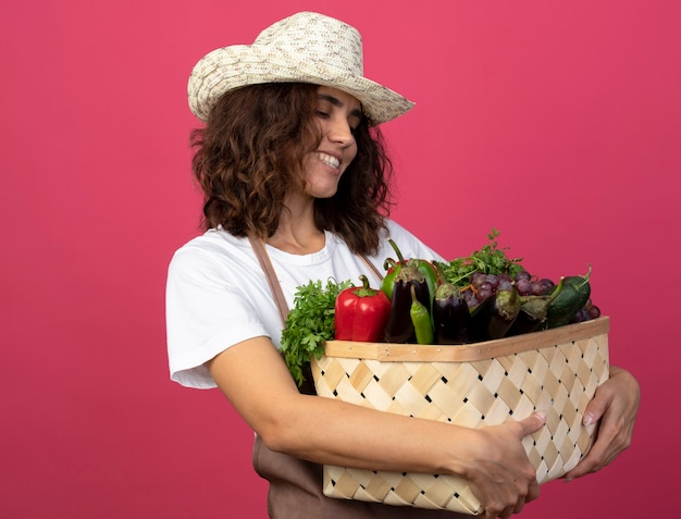 Smiling young female gardener in uniform wearing gardening hat holding and looking at vegetable basket