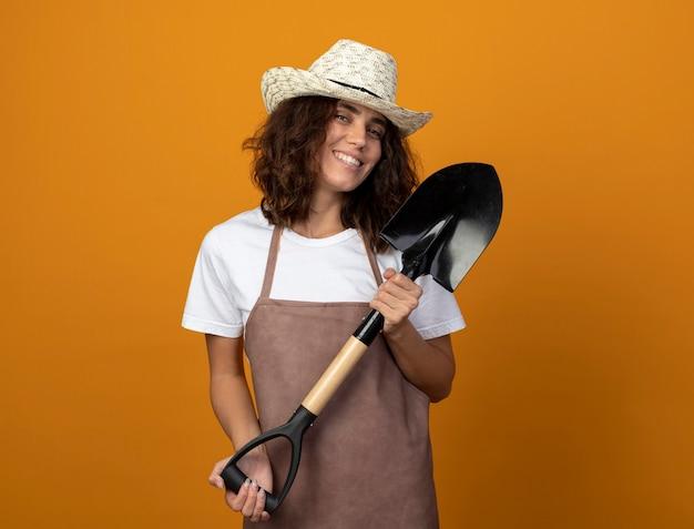 Sorridente giovane giardiniere femminile in uniforme che indossa cappello da giardinaggio azienda vanga