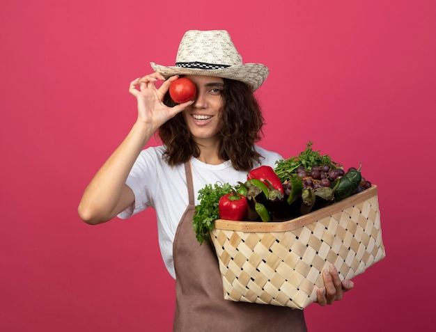 Smiling young female gardener in uniform wearing gardening hat holding vegetable basket showing look gesture with tomato isolated on pink