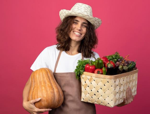 Sorridente giovane giardiniere femminile in uniforme che indossa cappello da giardinaggio tenendo il cesto di verdure con zucca isolato sul rosa