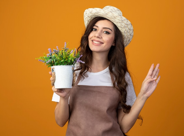 Smiling young female gardener in uniform wearing gardening hat holds flowerpot and gestures four with fingers isolated on orange wall with copy space