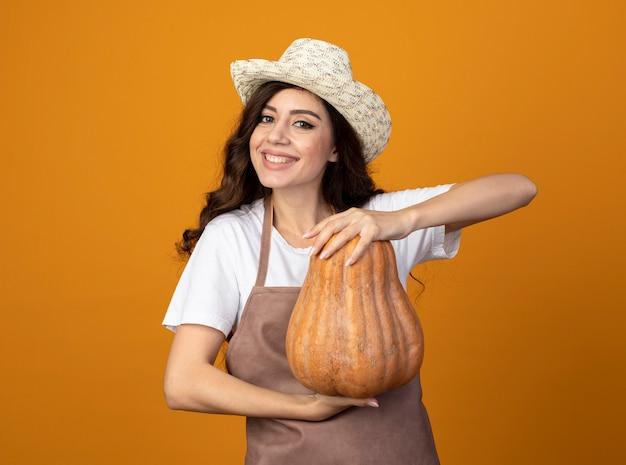 Il giovane giardiniere femminile sorridente in cappello da giardinaggio d'uso uniforme tiene la zucca isolata sulla parete arancione