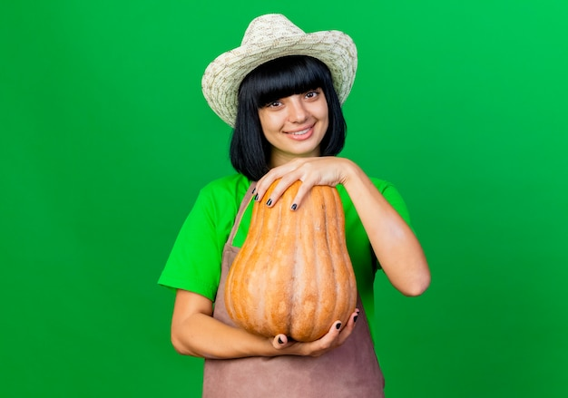 Il giovane giardiniere femminile sorridente in cappello da giardinaggio d'uso uniforme tiene lo sguardo della zucca