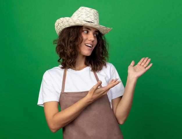 Sorridente giovane giardiniere femminile in uniforme che indossa il cappello da giardinaggio punta a lato con le mani