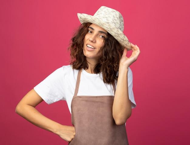 Sorridente giovane giardiniere femminile in uniforme che indossa il cappello da giardinaggio mettendo la mano sul hip tenendo il cappello isolato sul colore rosa