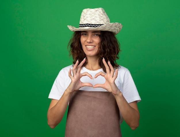 Sorridente giovane giardiniere femminile in uniforme che indossa il cappello di giardinaggio che mostra il gesto del cuore