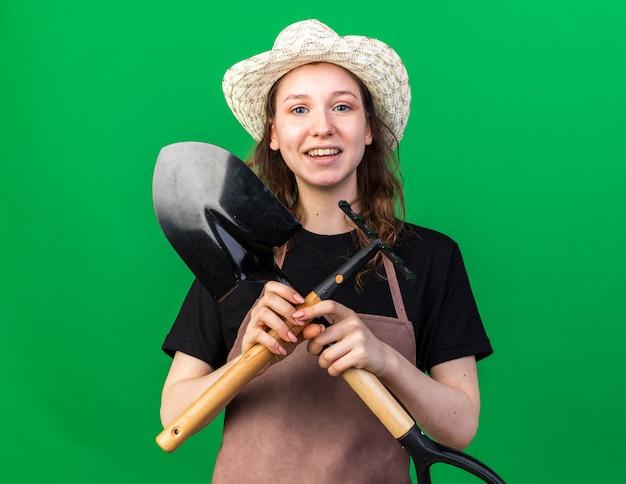 Sorridente giovane giardiniere femminile che indossa cappello da giardinaggio tenendo e attraversando la vanga con il rastrello