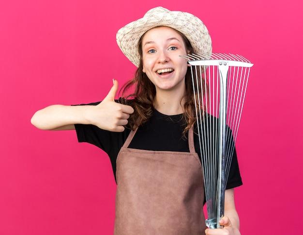 ピンクの壁に分離された親指を示す葉の熊手を保持しているガーデニング帽子をかぶっている若い女性の庭師の笑顔