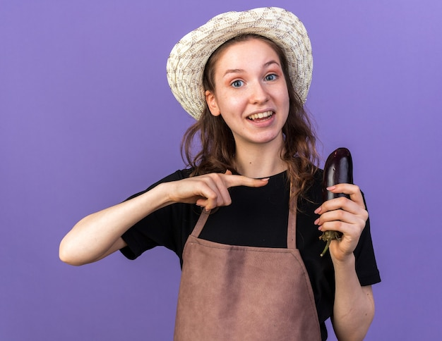 Smiling young female gardener wearing gardening hat holding and points at eggplant isolated on blue wall