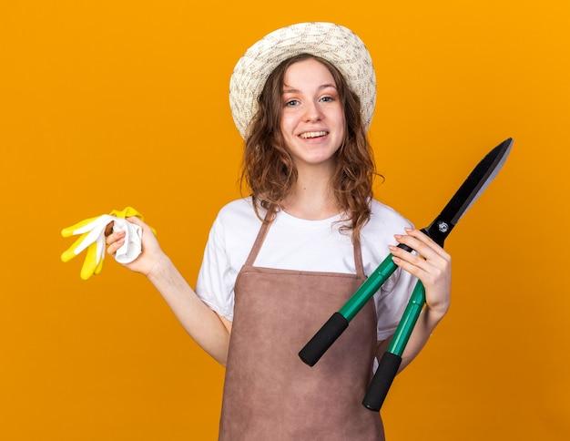 Sorridente giovane giardiniere femminile che indossa un cappello da giardinaggio che tiene la forbice da potatura con guanti isolati sulla parete arancione
