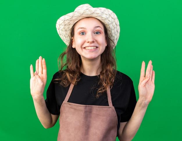 手を上げるガーデニング帽子をかぶって笑顔の若い女性の庭師
