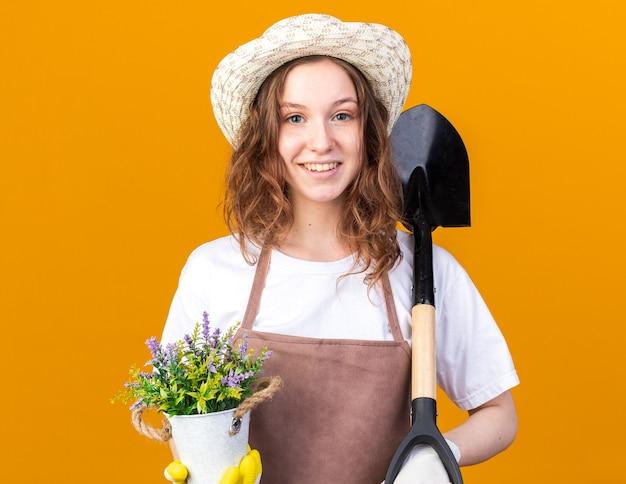 Sorridente giovane giardiniere femminile che indossa cappello da giardinaggio con guanti che tengono fiore in vaso di fiori con vanga isolato su parete arancione