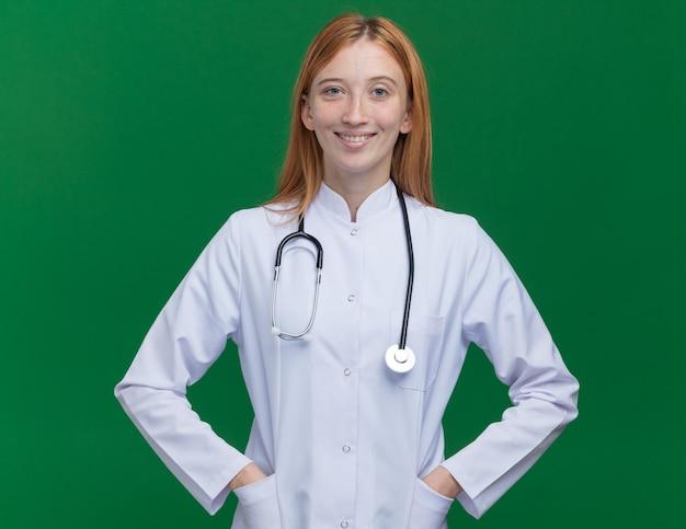 Улыбающаяся молодая женщина-рыжий врач в медицинском халате и стетоскопе держит руки в карманах
