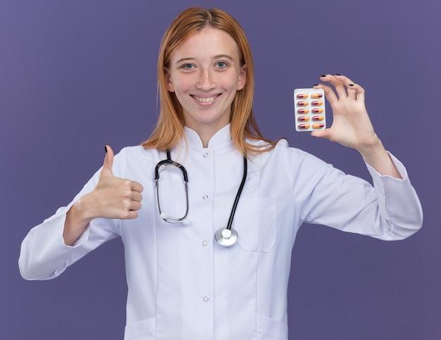 의료 가운과 청진기를 착용한 웃고 있는 젊은 여성 생강 의사는 의료용 알약 팩을 전면에 표시하고 보라색 벽에 고립된 엄지손가락을 보여주고 있습니다.